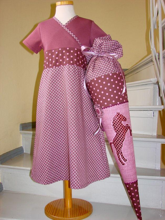 Das Kleid in Wickeloptik wird einfach wie ein T-Shirt über den Kopf gezogen. Das Oberteil ist aus weichem mauve-farbenen BW-jersey. Der Rock besteht aus wunderschön bedrucktem...