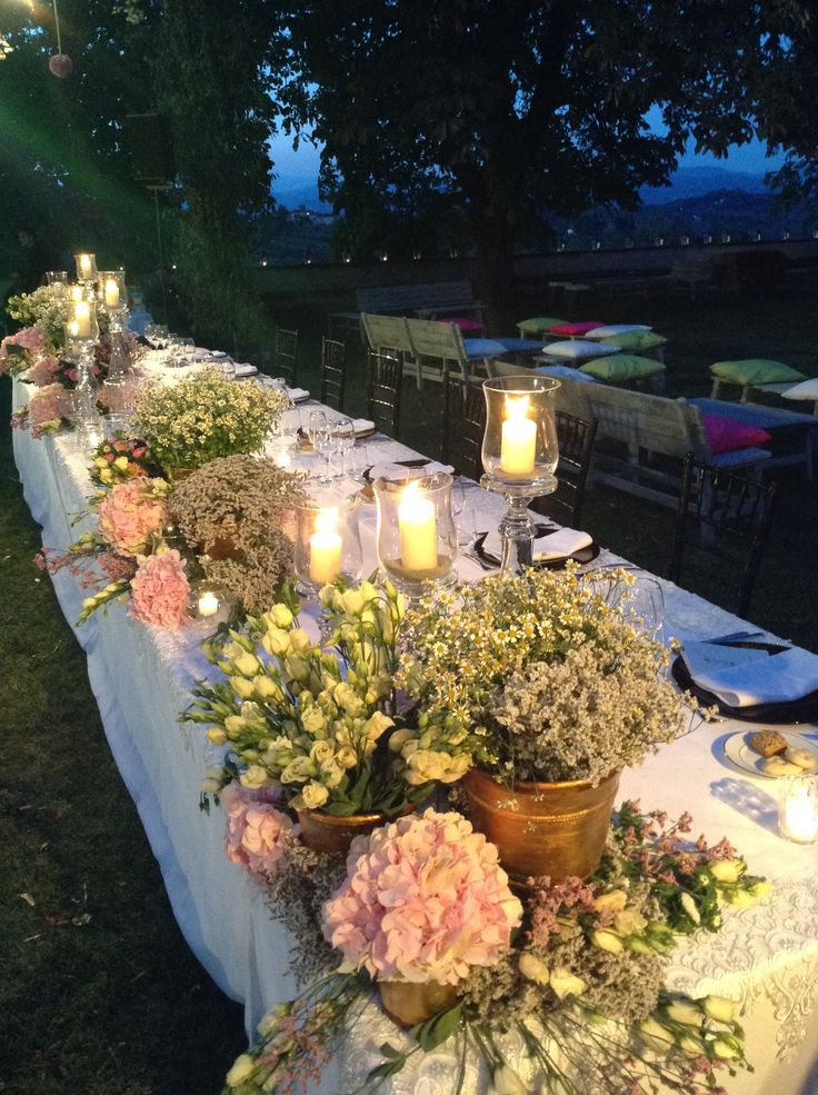 Mixed flowers in gold vases and glass candle holders