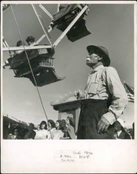 Carlos Lopez, an elderly Hispanic American man, looks up at ferris wheel at a carnival in San Luis (Costilla County), Colorado. 1950.