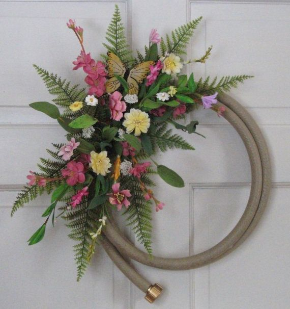 Country Garden hose wreath decorated with artificial ferns and flowers. A very unique door wreath