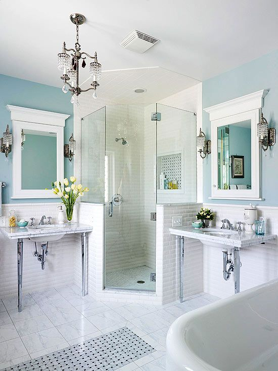 This airy bath exudes vintage charm at every turn. Matching console-style sinks, crystal light fixtures, subway-tile wainscoting, and a marble tile floor with decorative mosaic inset capture the character of yesteryear, while a roomy walk-in shower adds modern-day convenience.