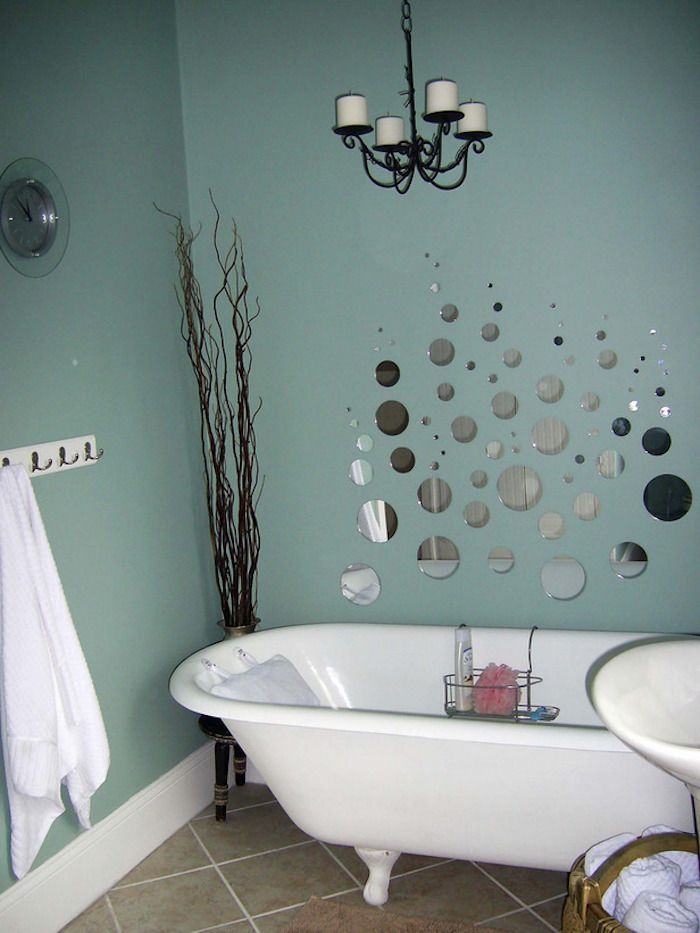 bathroom decorating ideas, duck's egg blue walls, one decorated with many round mirror segments, light brown floor tiles, white bathtub and tall dried plant in corner
