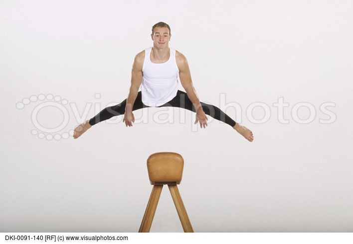 Gymnast in mid air vaulting the pommel horse.