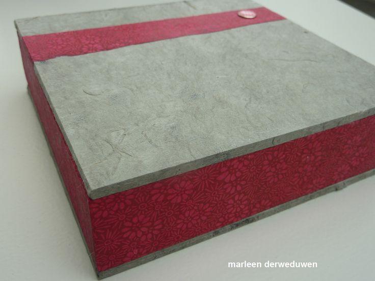 doos met handgeschept papier als bekleding en pin als versiering