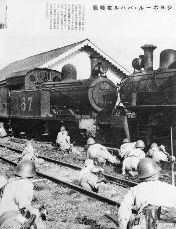 JOHORE, MALAYA. 1942-01-31. JAPANESE TROOPS TAKE COVER BEHIND STEAM ENGINES AT THE RAILWAY STATION IN THE FINAL STAGES OF THEIR ADVANCE DOWN THE MALAYAN PENINSULA WHICH CULMINATED IN THE SURRENDER OF ALL BRITISH FORCES, AND THE OCCUPATION OF THE BRITISH NAVAL BASE ON SINGAPORE ISLAND