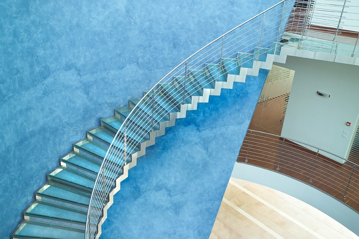 Helicoid staircase with modular stainless steel side structure and steps in float stratified glass and horizontal stainless steel rods banister