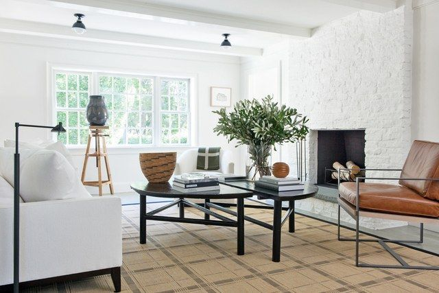 "In the family room, vintage Chinese demilune tables were cut down to cocktail height. ""I like that the two can be moved and interact with each other in a very nontraditional way,"" says Mazzarini. The custom-made sofa is covered in a Perennials fabric, the barrel chair is from RH, and the indoor-outdoor plaid rug is from Misha Carpet 