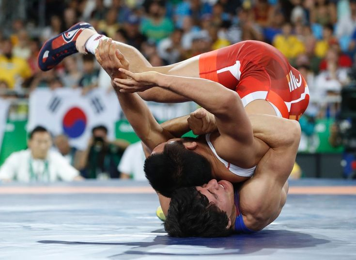 Azerbaijan's Rasul Chunayev (blue) wrestles with South Korea's Ryu Hansu in their men's 66kg greco-roman bronze medal match on August 16, 2016, during the wrestling event of the Rio 2016 Olympic Games at the Carioca Arena 2 in Rio de Janeiro. / AFP / Jack GUEZ