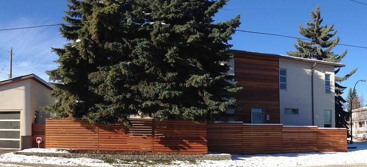 Dark Red Meranti horizontal strip fencing with matching horizontal tongue and groove siding. Hardwood supplied by Kayu Canada Inc. Work done by Meiga Developments.
