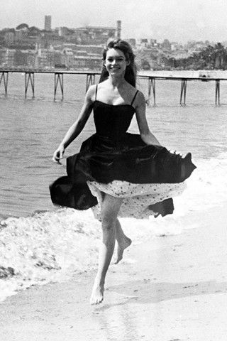 Brigitte Bardot  MAY 1956 – During the Cannes Film Festival, Brigitte took time to paddle in the Mediterranean wearing a full-skirted dress.
