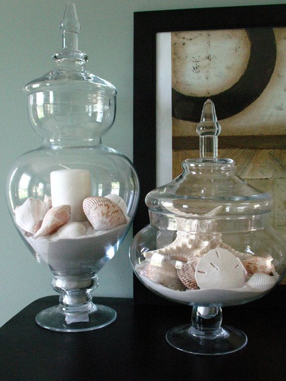 apothecary jars with sand, shells and candles to use them as candle holders