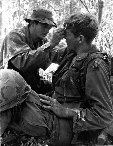 A wounded soldier of the 199th Light Infantry Brigade is tended to by a medic…