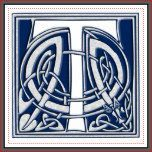 A beautiful, decorative embossed celtic letter illuminated with gray dragon heads on a velvety dark blue background.