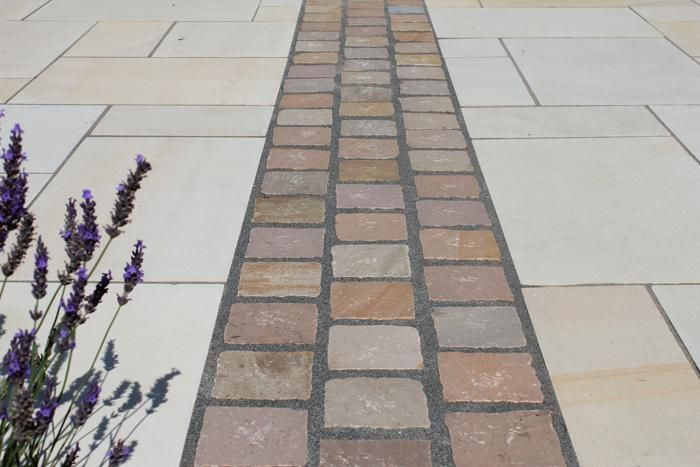 These Raj Green Sandstone Setts have been used to create definition and contrast with the sawn paving either side.