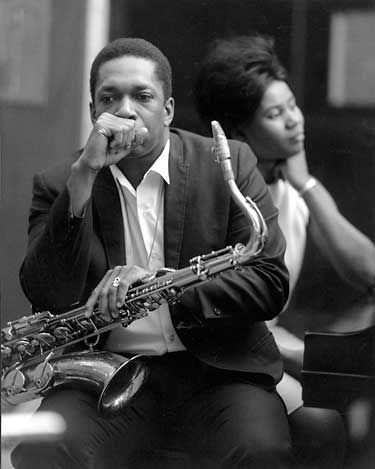 John Coltrane. I believe that's his wife Alice in the background. Alice McLeod was from Detroit and I believe he met her there in the vibrant, integrating Westside jazz scene. Legend has it he played Detroit a lot @ places like the Bluebird and the Minor Key.