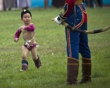 A Mongolian boy in costume runs past a member of guard of honor during the Naadam Festival in Ulan Bator, Mongolia Wednesday, July 11, 2012. Mongolians celebrate the anniversary of Genghis Khan's march to world conquest on July 11