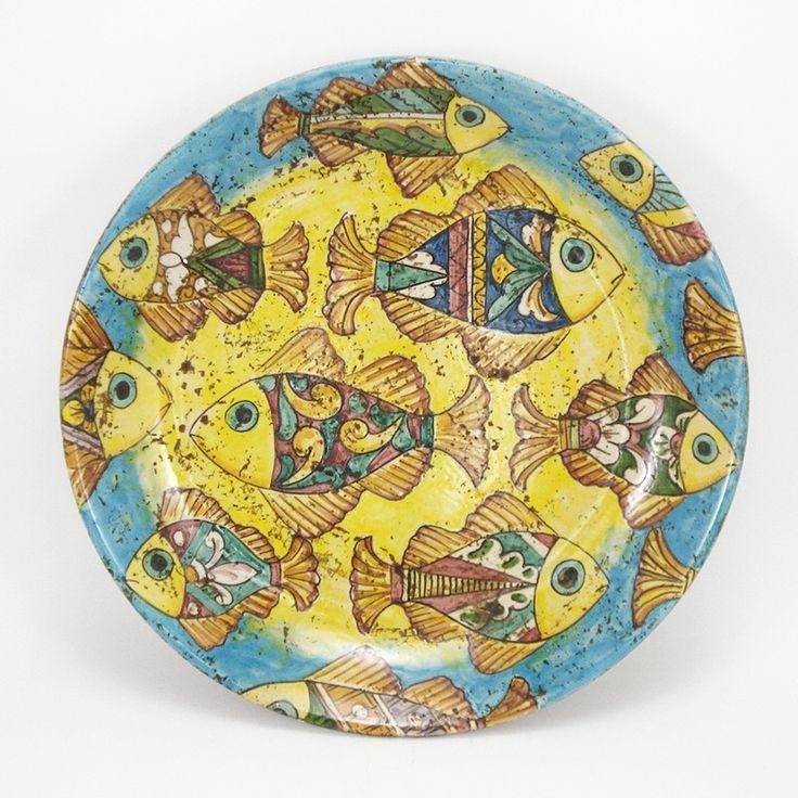 Piatto in ceramica da collezione, interamente dipinto a mano su fondo azzurro , sfumato Giallo Antico.  Contiene 9 pesci piu' ritagli disegnati e colorati singolarmente a mano.  Dimensioni cm 35.  Possibilita di avere altre dimensioni su richiesta