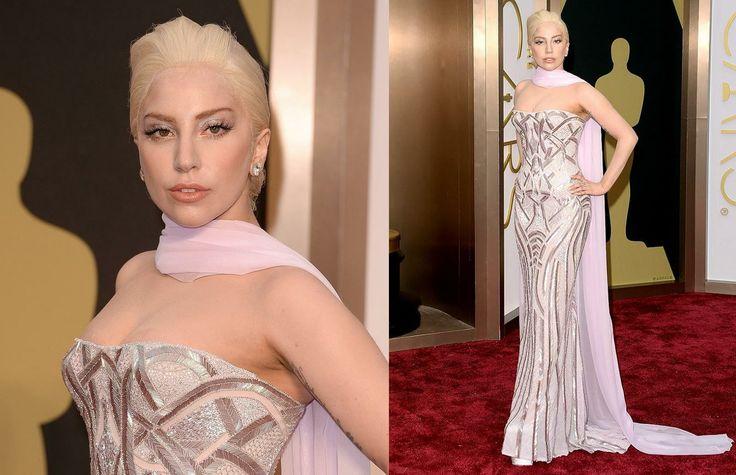"""Per una volta nella vita, Lady Gaga decide di stupirci """"al contrario"""" senza eccessi discutibili, ma indossando uno splendido abito metallic di Versace con un tocco retro dato dal morbido foulard. Ma i capelli? Guardate l'attaccatura sulla fronte: Noi temiamo fortemente che sia una parrucca... e voi? IL VOTO: 8 L'AGGETTIVO: Pericolosa"""