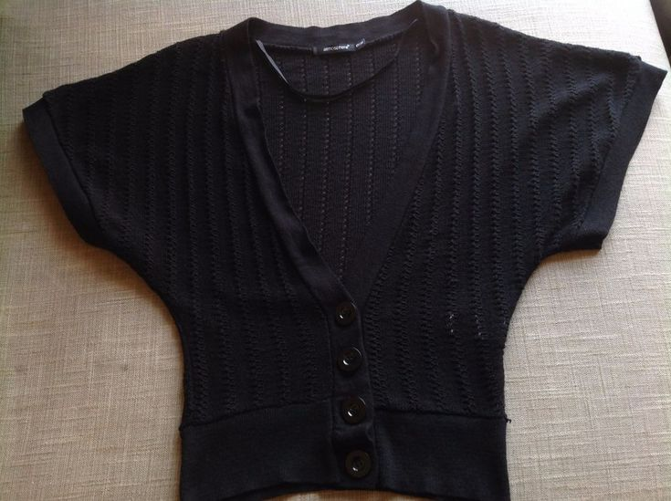 """Short-sleeved fine knit cardigan/shrug/bolero in black, cut in a bat-wing style. Plunging V-neck and fastens with four large plastic buttons. 50% cotton 50% acrylic blend. Waist (measured at the bottom hem) 14"""" across. 