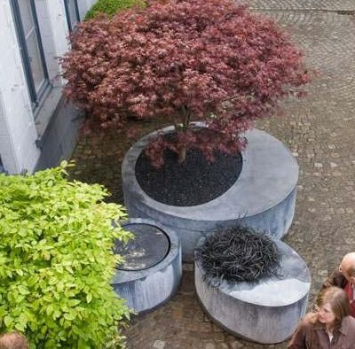 concrete planters - Jeg vil umiddelbart tro, at selvnivilerende beton kan bruges med fordel. Og tilsætter man pulverfarve før vandet, bestemmer man selv farven på plantekummerne... spørg i byggemarkedet.
