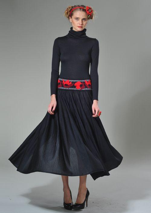 Однотонное платье приталенного силуэта. Длинный рукав. Высокий одинарный воротник, с отворотом, плотно охватывающий шею. Верхние детали платья соеденены широким поясом с жаккардовым орнаментом «маки». Объемная, длинная юбка-солнце.