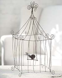 Fanciful but faux we think this delicate looking wire bird cage would look great anywhere in your home or garden.