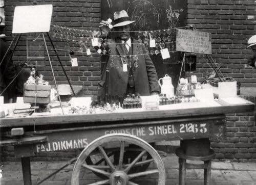 """Rotterdam - rommelmarkt, Handkar van de firma J. Dikmans Goudsche Singel 212. Op de kraam een serie brillen / ziekenfondsbrillen en een middel om vlekken te verwijderen. Tekst op het bord rechts: """" Weg met al de vlekken uit de kleeding'. juni 1932"""