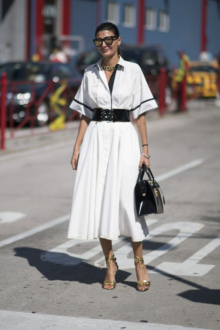 Giovanna Battaglia wears a white shirt dress with a lace-up patent black belt over the top