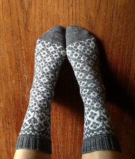 These socks start with a heart-draped garland that transitions into a series of interlocking wreaths. The wreath detail continues on the bottom of the foot.