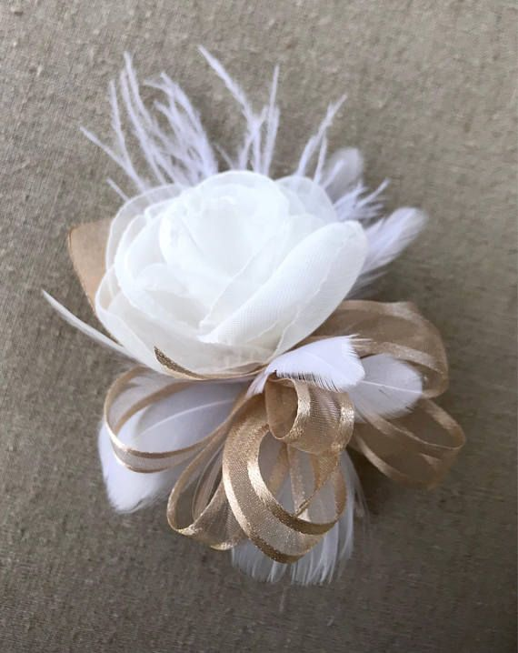 This beautiful one of a kind feather and organza flower corsage will be a lovely final touch to your wedding or special occasion look. Available in pin on (shown) or wrist. This corsage was made with a handmade fabric flower, feathers, and ribbon bow. Available in many colors, please