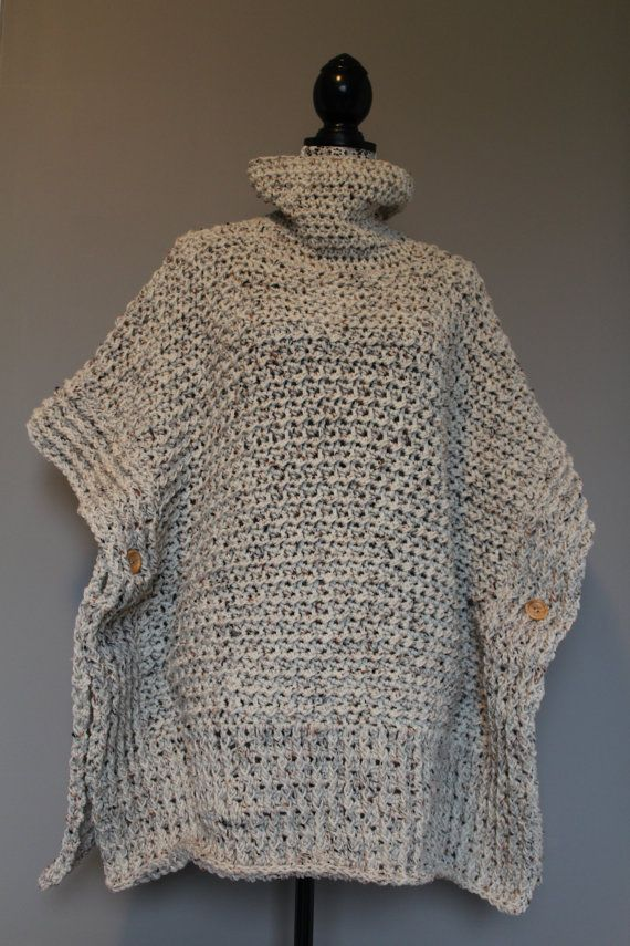 This oversized poncho is a medium size although would fit smaller women as well. Made from an off white acrylic yarn with brown and black