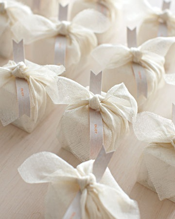 I like this as an idea for wedding favors: a tiny box with candy covered almonds, wrapped in a tied sheer square of fabric.