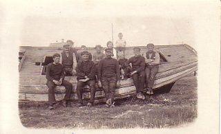 """Drivvodsfiskere, Fejø 12 personer ved drivkvase. Tekst på bagside: """"Flere drivvodsfiskere, der oprindelig stammer fra Kalvehave, slog sig ned på Fejø, hvor der var gode betingelser for ålefiskeriet. Yderst til højre bådebygger Carl Nielsen, Fejø. Han havde i sin tid ombygget den oprindelige Nordenhuse-sildebåd, der ses på billedet, til drivkvase. Yderst til venstre fisker Carl Bang, der havde flere fiskende brødre i Kalvehave. Ca. 1920. Fiskeri- og Søfartsmuseet"""