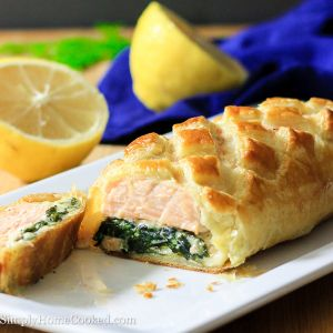 Skip out on making a basic salmon dish for New Year's Eve, and make this salmon wellington instead. The seasoned salmon is placed on a bed of cheesy sautéed spinach, wrapped in puff pastry, and baked to perfection. The baked puff pastry has a slight crunchiness yet soft doughy texture that takes a basic baked