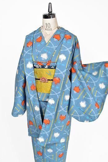 薄曇りの空のようなスモーキーでどこか愁いをおびたブルーをベースに、遠州椿をアレンジしたようなチューリップを思わせるお花模様がアクセントになったモダンデザインが織りだされたウールのアンサンブル(着物と羽織のセット)です。