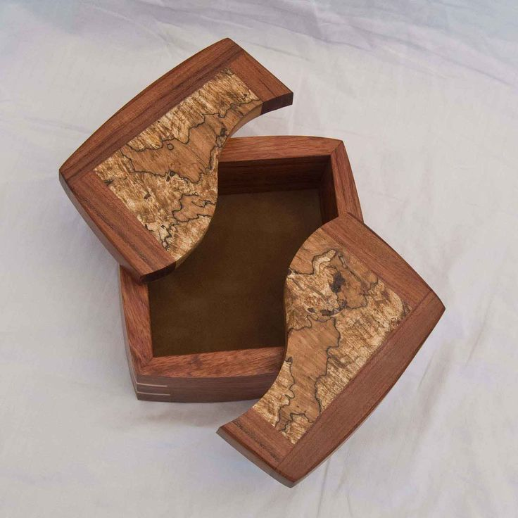 Four examples of a handmade decorative keepsake box with the lids open