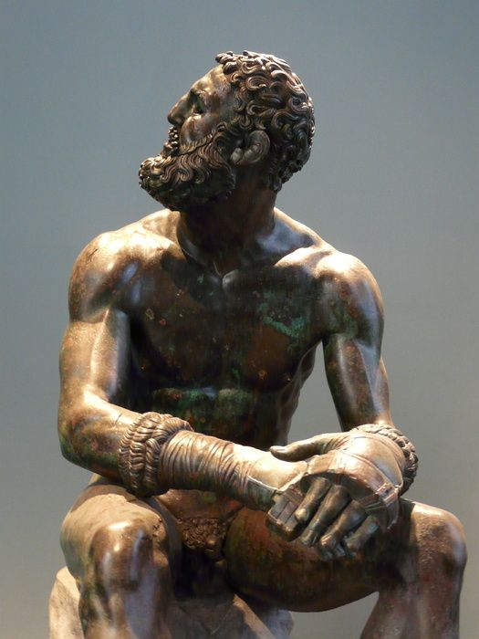 Seated Boxer a work of Lyssipus of Sikyon, a sculptor who worked for Alexander the Great, (or a work of Apollonius?, c. 225 BC ), Terme Museum Rome, Italy (Roman Copy 50 BC?). The boxer is wearing something like todays boxing gloves, the so-called himantes. He is looking maybe to the judges expecting the result of the box fight.