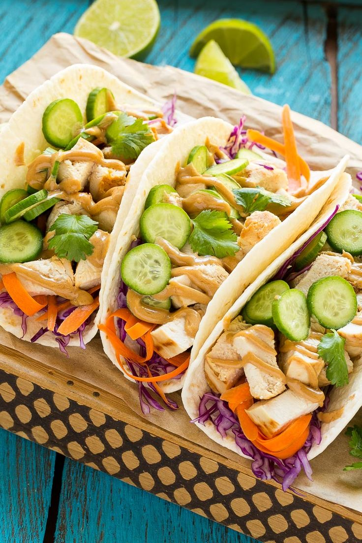 These thai chicken tacos are a quick and easy meal. Coconut marinated chicken is stuffed into warm tortillas with fresh vegetables and creamy peanut sauce.:
