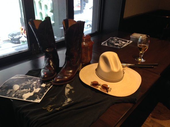 A memorial table for David Michael Greene contained his hat and cowboy boots.