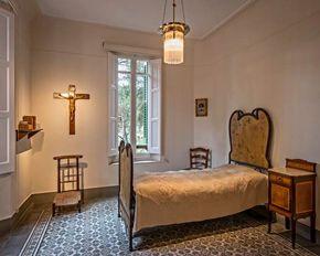 En 1906, Antoni Gaudí se instaló en la casa muestra del Park Güell con su padre, Francesc Gaudí i Serra, y con su sobrina, Rosa Egea i Gaudí. Francesc Gaudí había adquirido la casa en agosto de aquel año. Su padre murió en octubre de 1906, y su sobrina, en enero de 1912. Desde entonces, el arquitecto vivió solo en la casa. Imagen: El dormitorio de Gaudí en su casa en el Parque Güell, Barcelona.