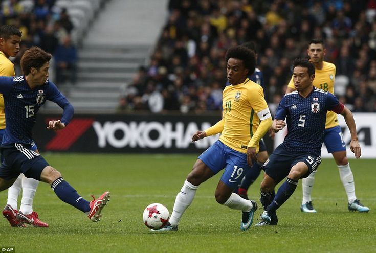 Willian dribbles with the ball and is closed down by Yuya Osako (left) and Yuto Nagatomo (right) during the first half