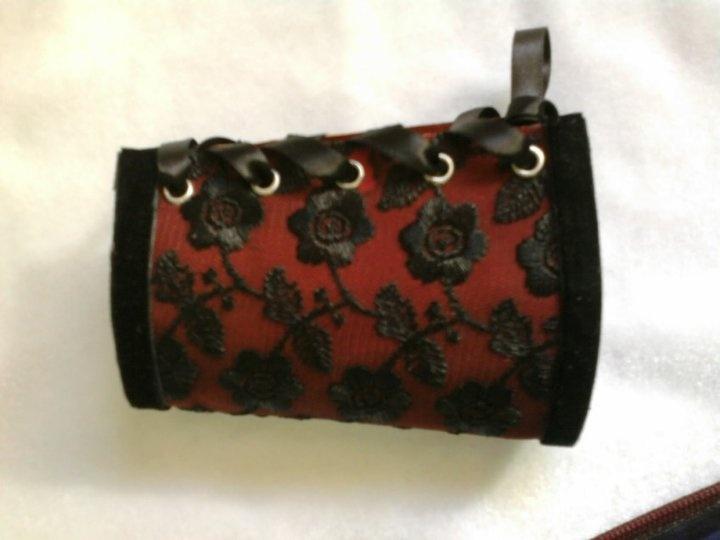 Red leather, black lace, black velvet ribbon, eyelets, black satin ribbon.