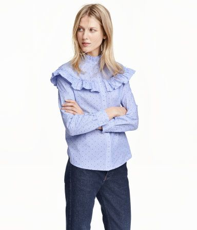 Straight-cut, long-sleeved blouse in woven cotton fabric. Stand-up collar, yoke with ruffle trim, and rounded hem with slits at sides. Slightly longer at back.