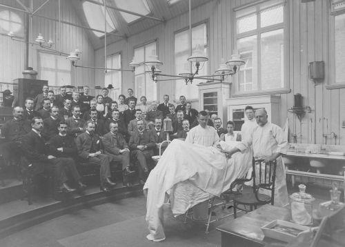 Opleiden was en is nog steeds 1 van de speerpunten UMCG,  foto; een patiënt voor de collegezaal, rond 1900
