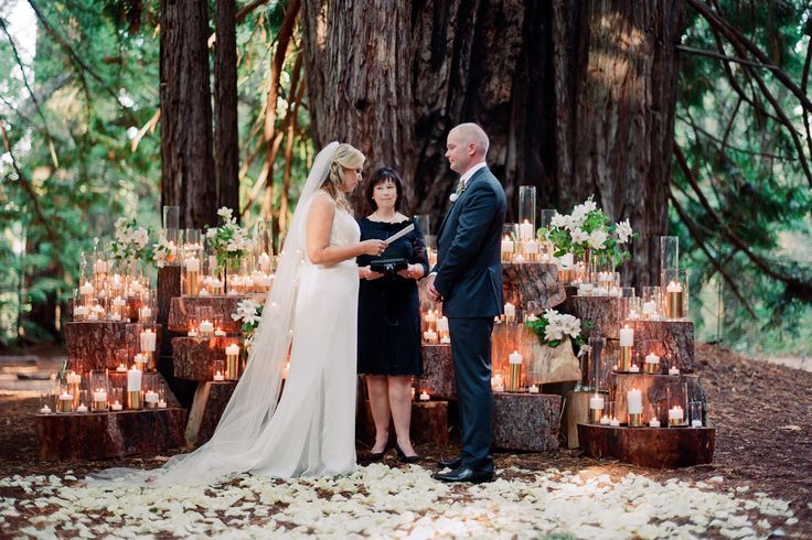 Wedding ceremony with shimmering signature Waterlily Pond candle alter under canopy of trees at Santa Lucia Preserve using stump sculpture of wood, gilded candles and white flowers. Tanja Lippert Photography. Design by Waterlily Pond Studio www.waterlilypond.com. Tanja Lippert Photography.
