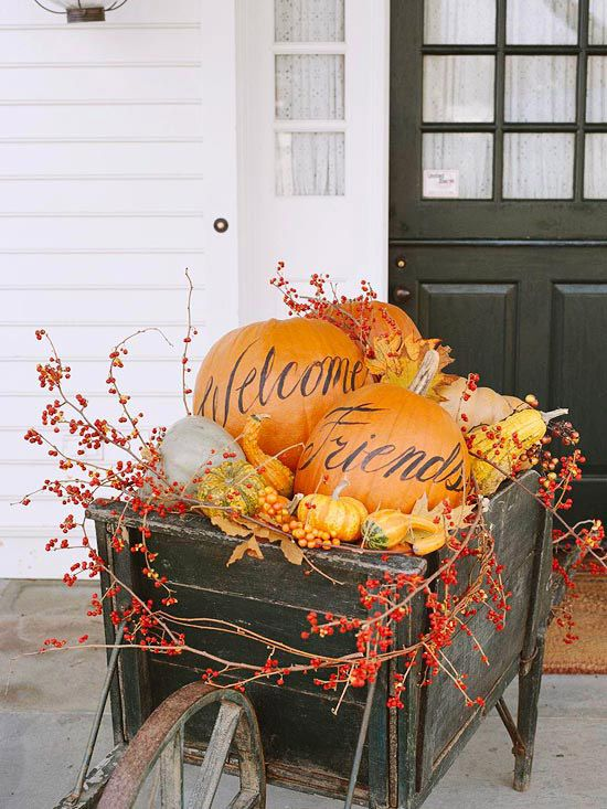 Pumpkins, gourds, leaves, and berry vines make for a festive front entry! Get more pumpkin and fall entry decorating ideas.