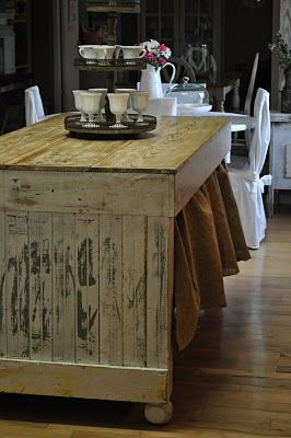 chippy white painted island with burlap skirt to hide the shelf of appliances