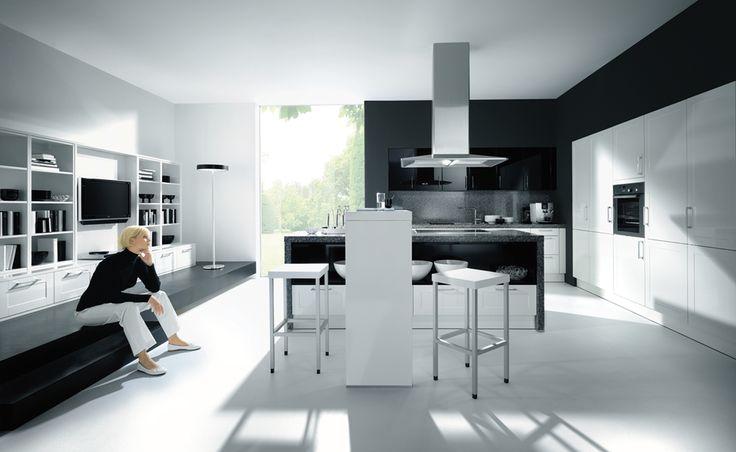 Moderne witte keuken met zwarte muren en zwart kookeiland met granieten werkblad als contrast. De grijze kleur van de dampkap en keukenstoelen zorgen voor een extra, meer neutrale kleur