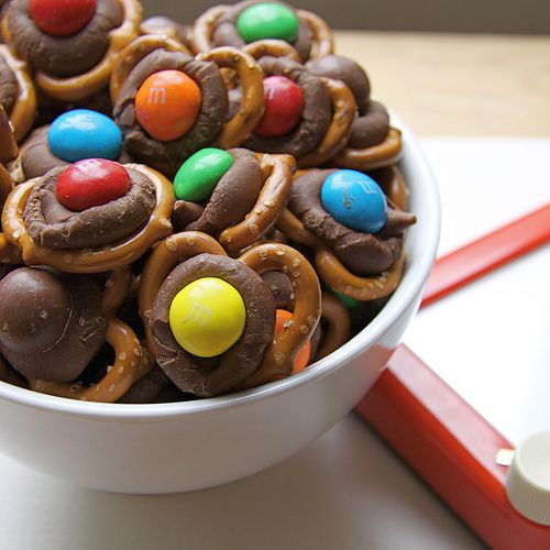 Hershey's kiss Pretzel treats. They're SO easy! You can buy holiday colored M&M's so they are Christmas/V-day/Halloween, etc. HOW TO: Melt Hershey's kisses onto tiny twist pretzels (225 degrees, 3-5 minutes)