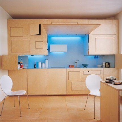 Cuisine escamotable en bouleau clair avec lumière bleue et chaises blanches